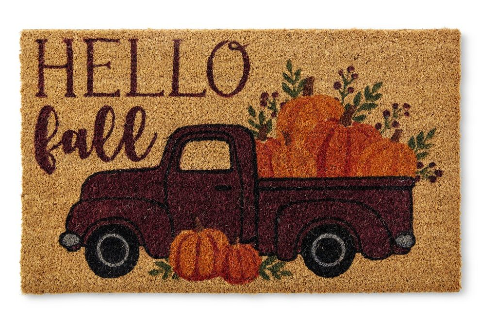 fall front doormat that says hello fall with a pickup truck full of pumpkins